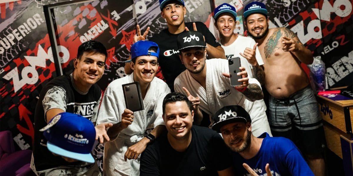 8 pessoas sorrindo para foto, um segurando iphone 11 pro