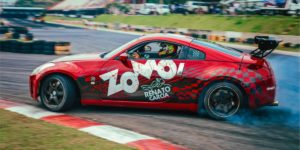 Carro nissan 350z vermelho com adesivos da zomo fazendo drift derrapando