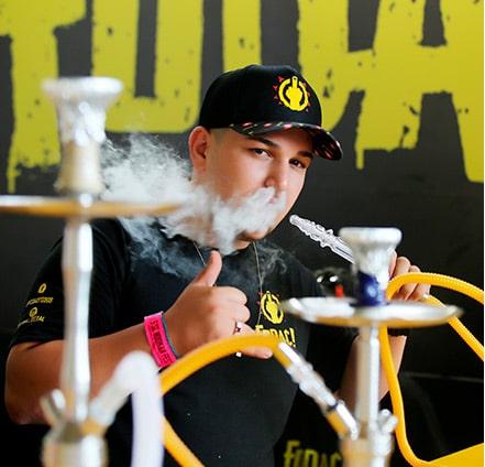 Homem fumando narguile e soltando multa fumaça