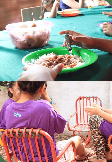 Crianças com um prato de comda comendo